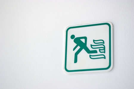 fire exit sign: Fire exit sign on white wall Stock Photo
