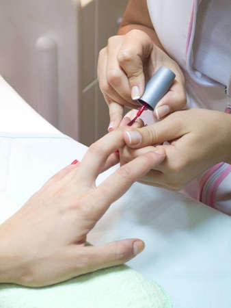 costumer: Manicurist putting red nail polish on costumer Stock Photo