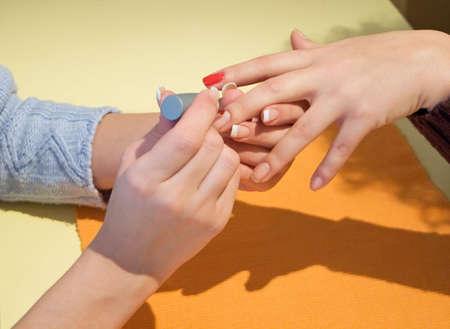 french manicure sexy woman: Manicurist putting red nail polish Stock Photo