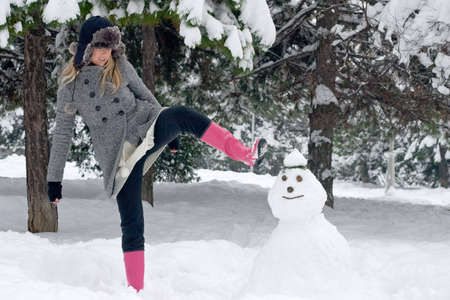 Angry girl in winter clothing is about to kick snowman