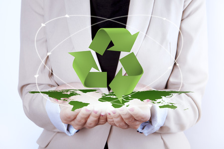 suggesting: 3D Recycling Symbol over digitally generated earth map in woman hands. Woman is suggesting let us think ECO and take care of the earth. Digitally generated elements are in green color.