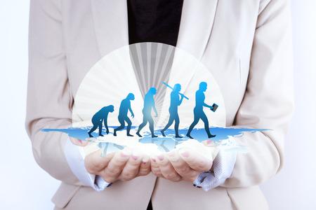 origen animal: Crecimiento La evolución humana en manos de la empresaria. Foto de una empresaria de la mujer con las manos extendidas holding imagen generada digitalmente de una evolución o un símbolo del crecimiento humano. Última evolución sujeto está llevando dispositivo inteligente.