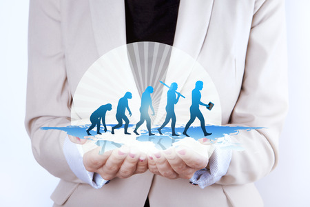 Human evolution  Growth in businesswoman hands. Photo of a woman  businesswoman with hands extended holding digitally generated image of a human evolution or symbol of growth. Last evolution subject is carrying smart device.