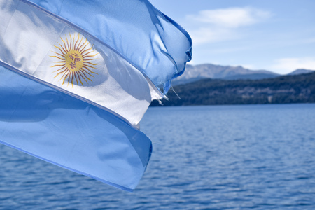 Argentinian flag waving on Nahuel Huapi Lake, Andes mountains background.