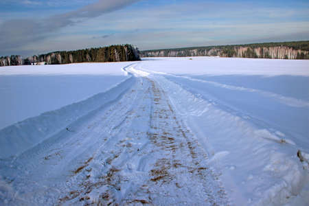 Beautiful scenery. The winter road cuts deep into the snow and runs, curving and losing itself in the forest.