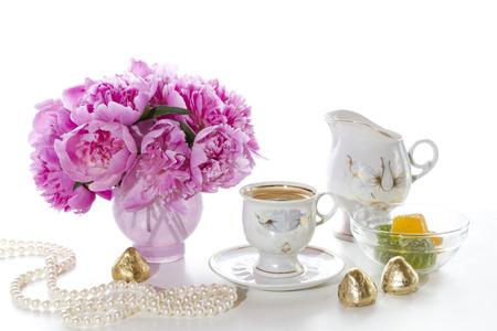 Morning coffee, a bouquet of peonies and pearls on white background. photo