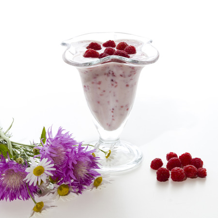 liszt: Yogurt with raspberries in a transparent vase and flowers on a white background.