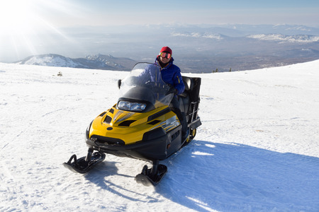 urals: Athlete on a snowmobile moving  in the mountains of the Southern Urals.