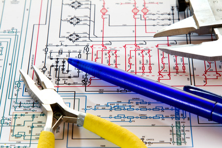Pliers, handle and caliper lie on the electronic circuit.