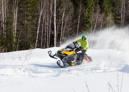 Athlete rides in the winter woods on a snowmobile. Banque d'images