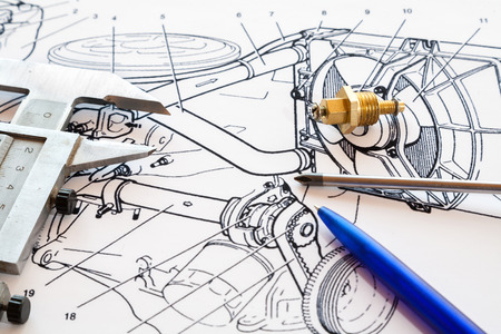 Caliper, screwdriver and pen lie on the drawing.