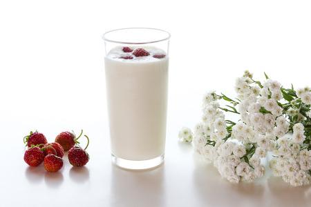 latte fresco: Yogurt con fragole e un bouquet di fiori bianchi su uno sfondo bianco.