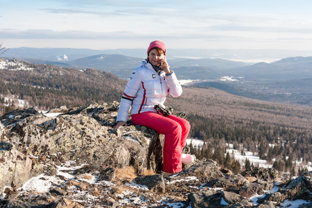 urals: Woman talking on a cell phone on top of the mountain. Access mobile communication anywhere in the world. March in the southern Urals.