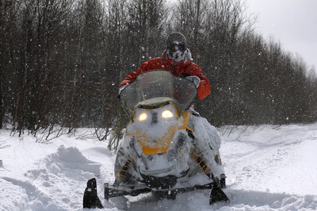 Sportsman, snowbound, riding a snowmobile in the winter woods. Stok Fotoğraf