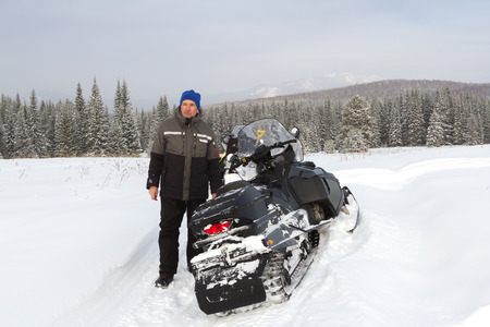 admires: The man stopped to rest while traveling on a snowmobile in the mountains of the Southern Urals. He admires the beauty of his native land. Stock Photo