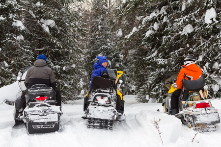 Three friends traveling by snowmobile in the mountains and forests of the Southern Urals. Banque d'images