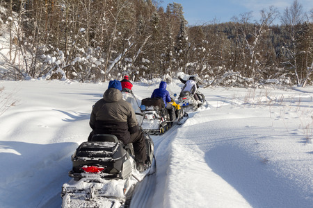 Athletes snowmobile stopped in a clearing in the mountains of the Southern Urals.