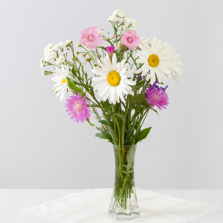Bouquet Of Daisies And Cornflowers In A Glass Vase On A White