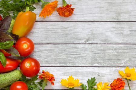 produits alimentaires: Légumes, le persil et le basilic, des fleurs sur fond de bois.