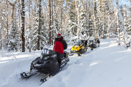 Three snowmobiles and a girl in winter birch forest. Banque d'images