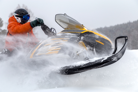 urals: Athlete on a snowmobile moving in the winter forest in the mountains of the Southern Urals.