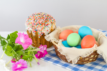 Basket with Easter eggs and Easter cake on a light background.