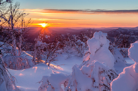 ural: Christmas sunset in the Ural Mountains. The last rays of the setting sun. Stock Photo
