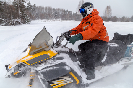 urals: The sportsman on a snowmobile moving through deep snowdrifts in the winter forest in the mountains of the Southern Urals.