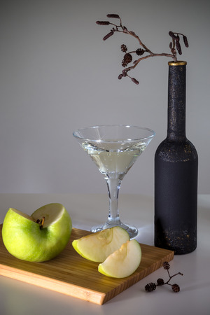A glass of martini and a cut apple on a cutting board. Stock Photo