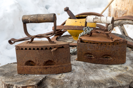 Two old rusty irons on a large wooden stump. Stock Photo