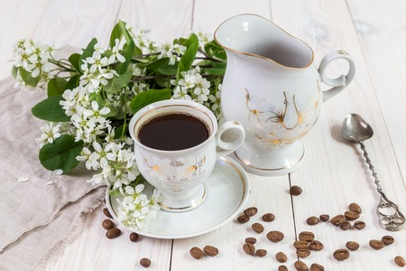 A cup of coffee and a bouquet of bird cherries on a wooden table. Stock Photo