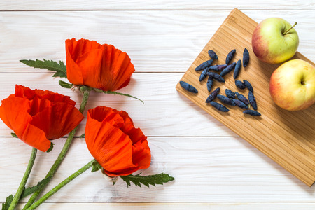 Three poppies on a wooden background. Place for the text. Stock Photo
