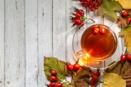 A cup of hot tea among the autumn leaves and berries on a wooden background.