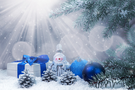 Snowman and Christmas decorations on a snow-covered background. Space for text.