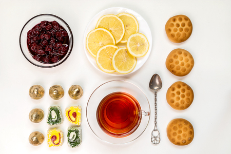 Tea with lemon and sweets on a light background. Food-knolling.