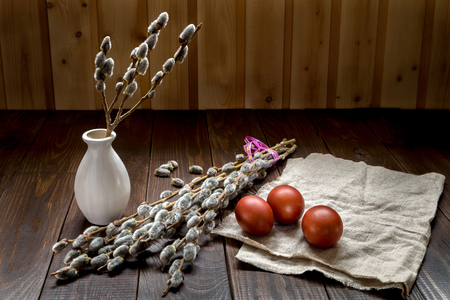 Still life with a pussy-willow and Easter eggs on a wooden background.