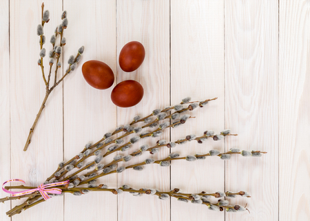 A bunch of willow branches and Easter eggs on a wooden background. Space for text.