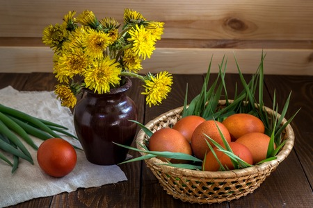 Easter eggs and a bunch of dandelions on a wooden table. Stock Photo