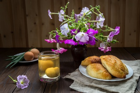 Pies and a bouquet of petunias on a wooden table. Stock Photo