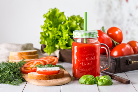 Tomato juice and a sandwich on a wooden table. Stock Photo
