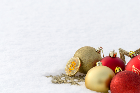 Christmas decorations and bitcoin lying in the snow in a clearing. Stok Fotoğraf - 108329667
