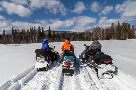 Three friends on snowmobiles in the mountains of the Southern Urals.