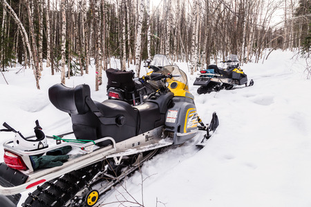 Three snowmobiles in the winter forest in the mountains of the Urals.