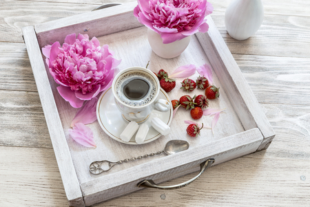 Coffee with marshmallow and strawberries on a light wooden background.
