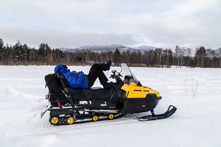 A woman is resting on a snowmobile and admiring the mountains of the Urals.