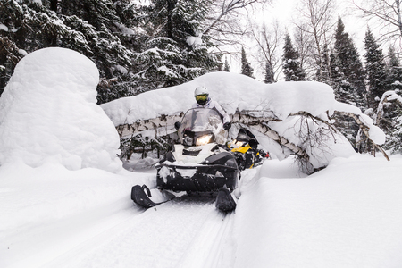 Woman on a snowmobile moving in the winter forest in the mountains of the Southern Urals.