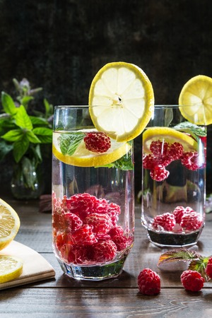 Refreshing drink with raspberries, lemon and mint on a dark background.