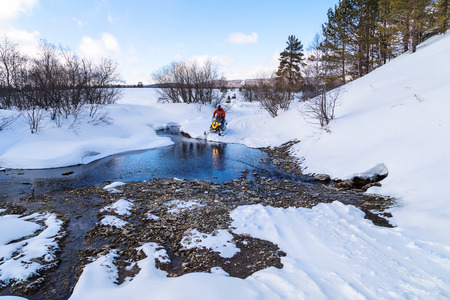 Athlete on a snowmobile forwarded across a river in the mountains of the Urals.
