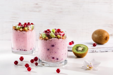 Smoothies with yogurt, granola, kiwi and cranberries on a light background. Imagens - 120879744