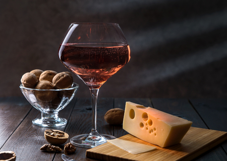A glass of rose wine, Maasdam cheese and walnuts on a dark background.